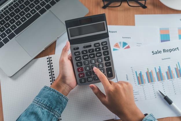 회계사의 손이 계산기를 사용하고 있습니다. 비용 분석을 위해 손익 및 세금 계산 개념 재무 제표 작성
