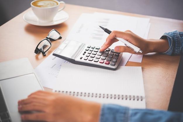 会計士の手は、電卓を使用しています。コスト分析に損益計算書、税額計算のコンセプト作成、財務諸表の作成