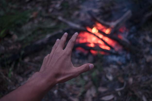 Взрослый мужчина греет руки у костра в лесу.
