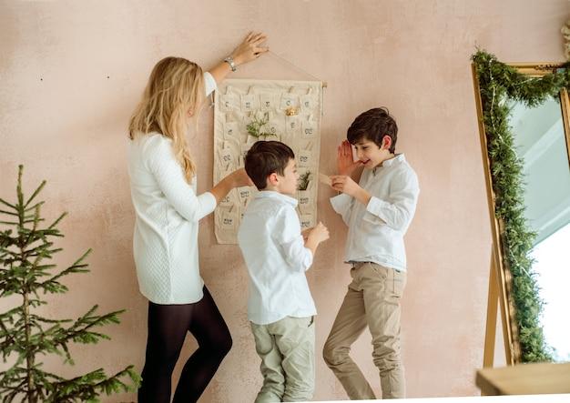 Адвент-календарь висит на стене. подарки-сюрпризы для детей. два эмоциональных мальчика