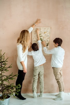 壁に掛かっているアドベントカレンダー。子供のための贈り物の驚き。 2人の感情的な男の子
