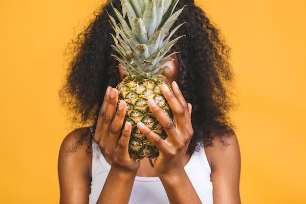 Афро-американская темнокожая веселая девушка держит в руках ананас