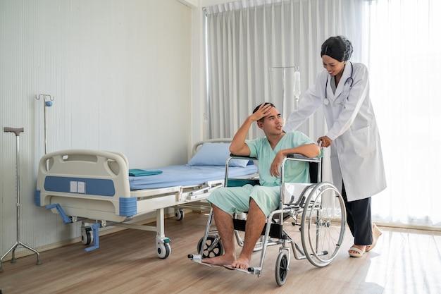 Афро-американский врач толкает инвалидную коляску и консультирует по вопросам лечения пациентов, сидящих в инвалидной коляске, и внимательно следит