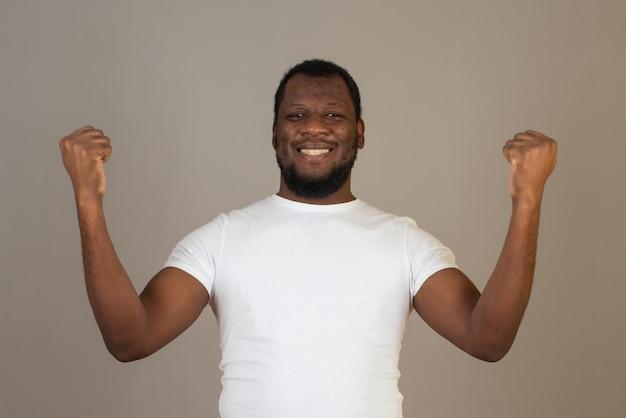 灰色の壁の前に立っているアフリカ系アメリカ人の喜び、幸せな男。