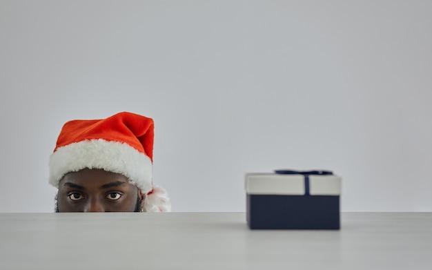 贈り物を持ってテーブルから見ているサンタの帽子をかぶったアフリカ人