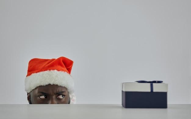 산타 모자를 쓴 아프리카 남자가 선물을 들고 테이블에서 바라보고 있다
