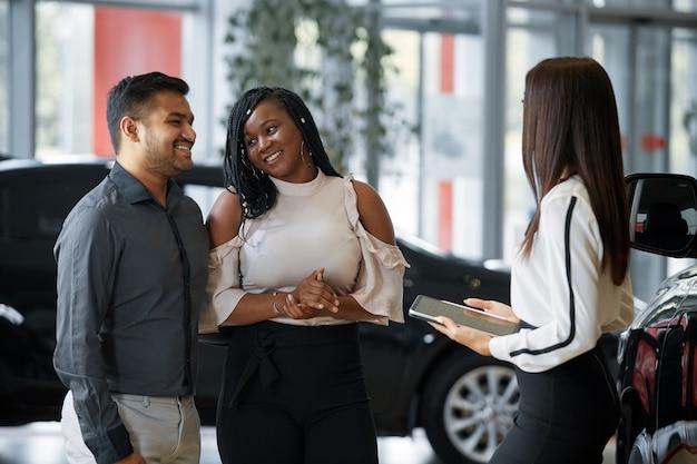 エージェントは、自動車販売店の若いカップルに高級車の新機能を紹介します。
