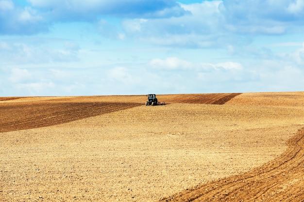 Сельскохозяйственное поле, которое вспахано трактором, готовит почву для посадки. весна