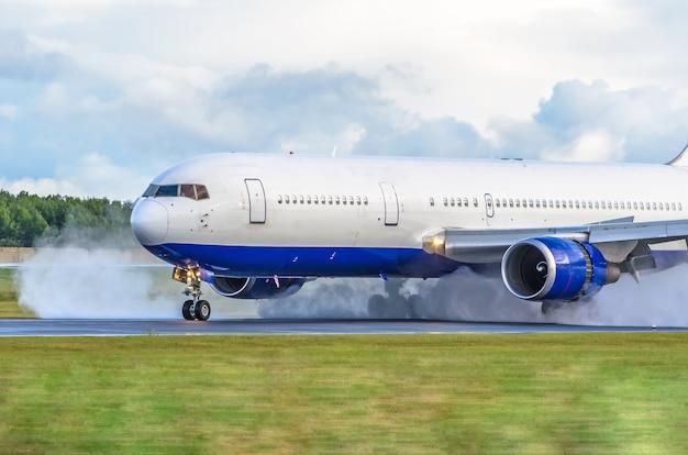 Самолет с реверсивным двигателем на мокрой взлетно-посадочной полосе.