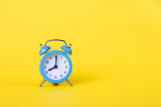 Будильник показывает 8 утра. утреннее время. циферблат. желтая стена, концепция крайнего срока. скопируйте пространство, пустое место для текста.