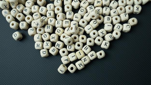 教育概念の黒い背景の上のアルファベットの木製の立方体