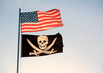 The American flag and pirate flag flying from flagpole