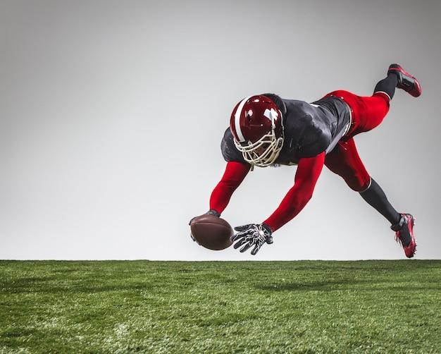 Игрок в американский футбол в действии на зеленой траве и сером фоне. Premium Фотографии