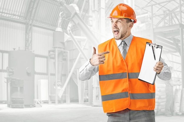 建設ベストとオレンジ色のヘルメットの叫び声で怒っているビルダー。安全スペシャリスト、エンジニア、業界、建築、マネージャー、職業、ビジネスマン、仕事の概念