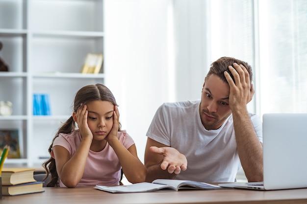 怒っている父と娘が机で宿題をしている