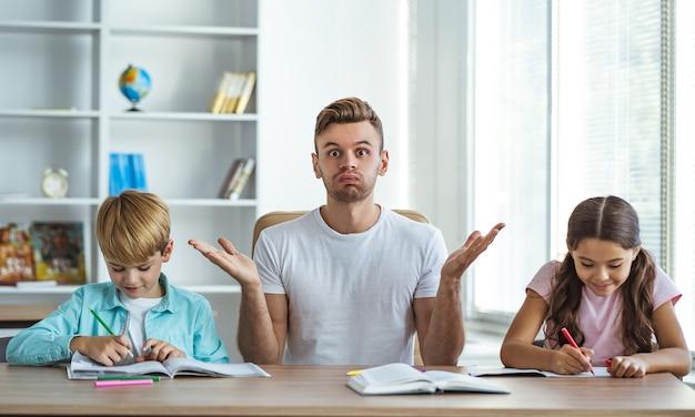 机で宿題をしている子供たちと怒っている父親