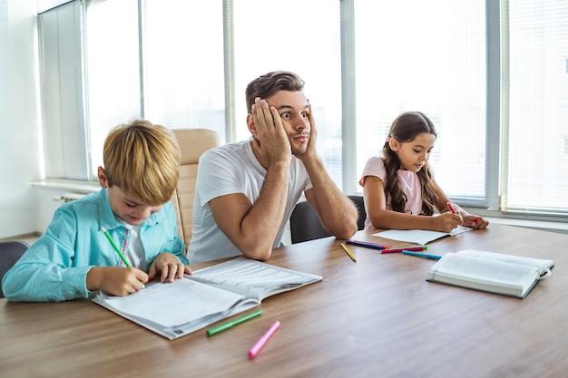 식탁에서 아이들과 숙제를 하는 화난 남자