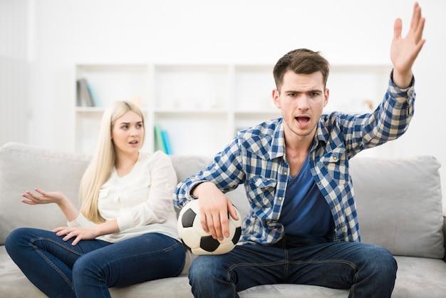 화난 남자는 축구를 보고 소파에 있는 여자 근처에서 몸짓을 한다