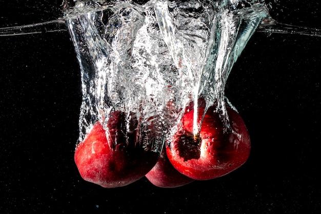 黒い背景でスポンジが美しく裂けるまで、リンゴは黒い水に落ちます。