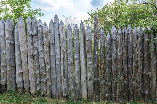 사과 과수원은 오래된 풍화된 통나무 울타리로 울타리가 쳐져 있습니다. 골동품 나무 울타리
