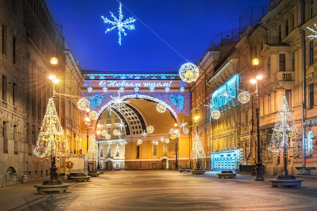 Триумфальная арка на дворцовой площади в санкт-петербурге и новогодние украшения в свете синей зимней ночи. надпись: с новым годом!