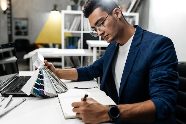 眼鏡と青いジャケットを着た建築家は、オフィスの机で色のカタログを扱っています。
