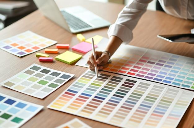 建築家はカラーチャートを比較し、タブレットを使用しています。