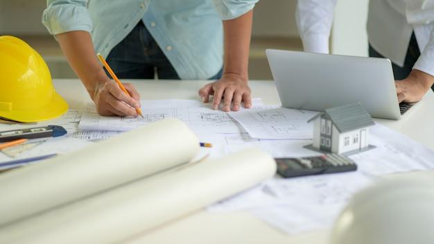 Архитектор редактирует план дома в соответствии с требованиями заказчика. Premium Фотографии