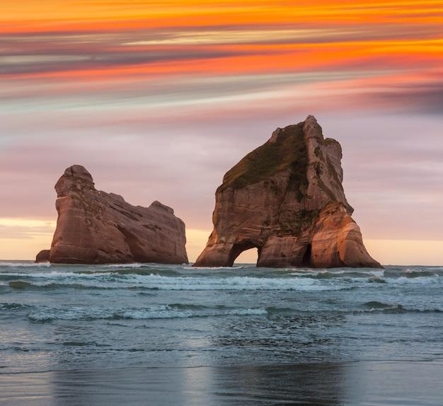 Острова арки wharariki beach на закате в новой зеландии