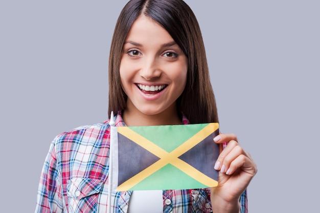 우정에는 국경이 없습니다. 회색 배경에 서 있는 동안 자메이카의 행복한 젊은 여성 국기