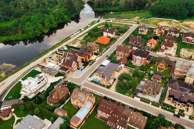 Район коттеджного городка с элитными домами премиум-класса на земельном участке. концепция строительство и продажа загородной недвижимости.