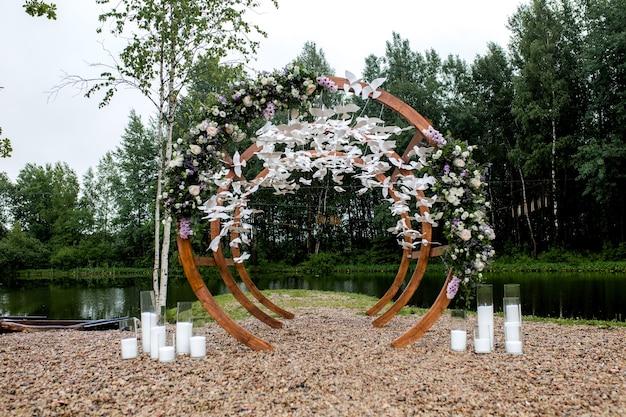 Площадка для свадебной церемонии в лесу, у реки на пристани. деревянная круглая арка украшена цветами, зеленью, белыми птицами, свечами, стульями, скамейками для гостей. симпатичный, стильный декор