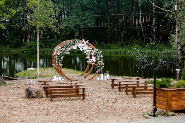 桟橋の川の近くの森の結婚式のエリア。花、緑、白い鳥、キャンドル、ゲストのための椅子のベンチで飾られた木製の丸いアーチ。キュートでスタイリッシュなインテリア