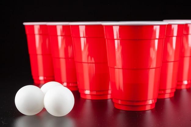ビアポンのゲームのための赤いプラスチックカップの配置