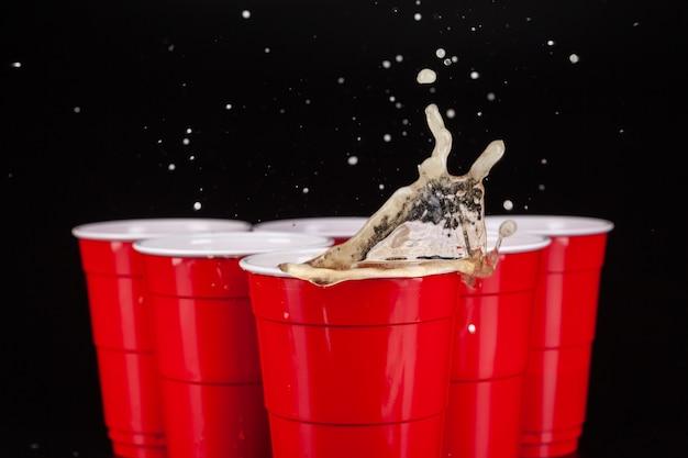 ビールポンのゲームのための赤いプラスチックカップの配置