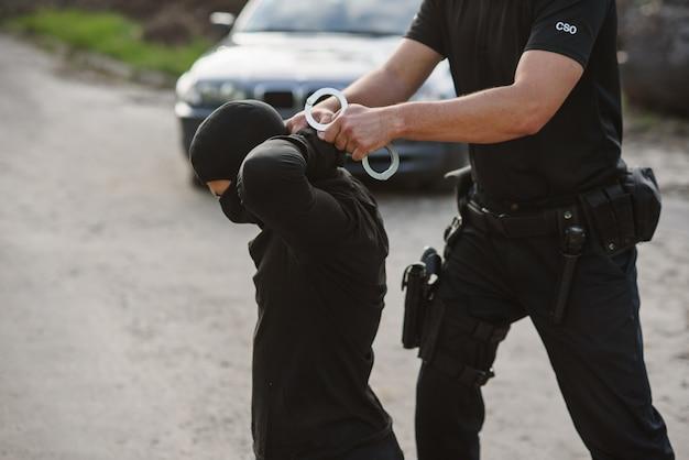 逮捕された犯罪者はひざまずいており、警官は彼に手錠をかけています。法と秩序。