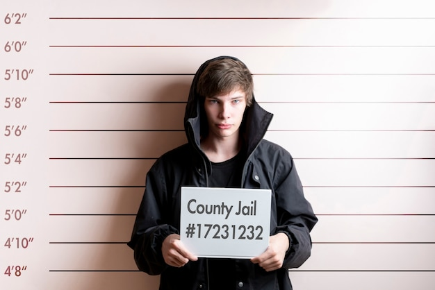 체포 된 죄수 청년이 신장 차트 앞에서 장소 카드를 들고