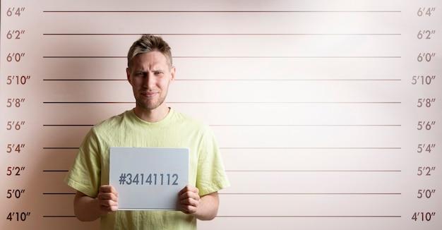 Арестованный заключенный молодой человек держит карточку перед таблицей роста