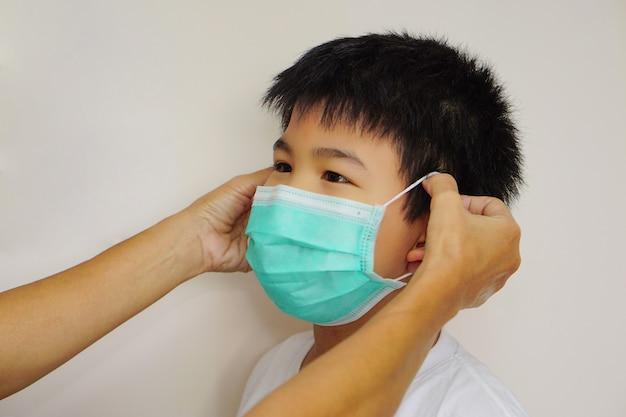 Мать азиатского мальчика надевает на своего ребенка медицинскую маску для защиты и сопротивления микробам, которые распространяются в воздухе. концепция здоровья, лечения и гриппа.