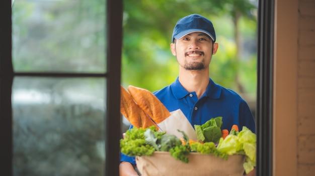 アジアの配達員が食料品店から彼女の家の前の女性にバッグを与える