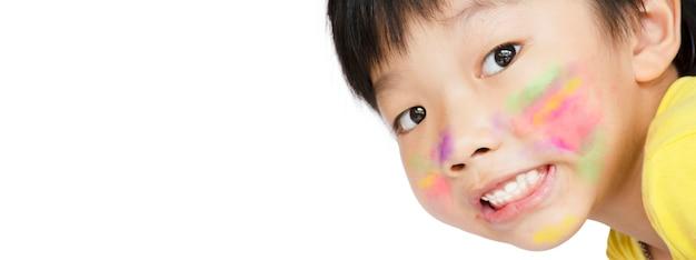 アジアの小さな男の子は微笑んで、コピースペースで白い背景の彼の顔に水彩絵の具の塗抹標本を持っていた