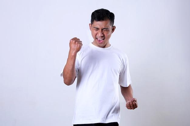 Азиатский мужчина в белом носил выражение радости и победы, изолированное на белом фоне