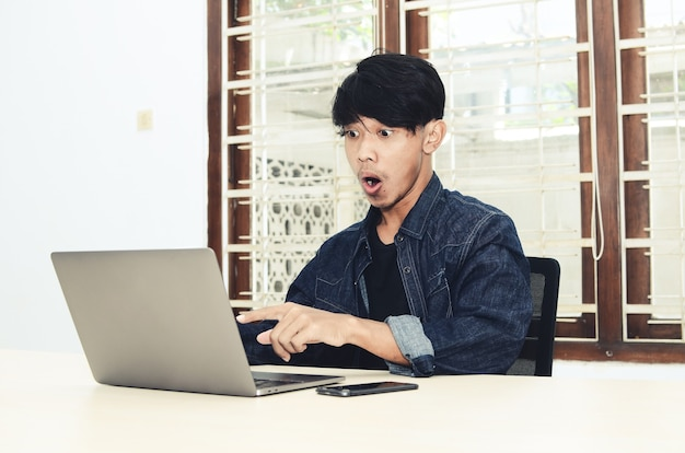 Азиатский мужчина сидел перед ноутбуком с шокированным выражением лица.