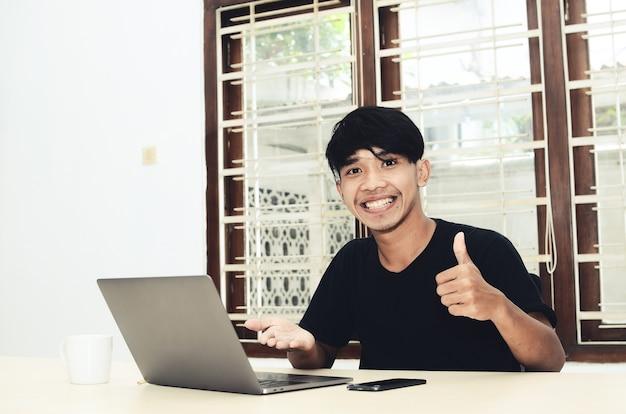 アジア人の男性がノートパソコンを指差して座っていた
