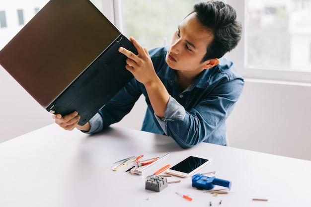 アジア人男性はそれを修理するために壊れたコンピューターを取り出していた