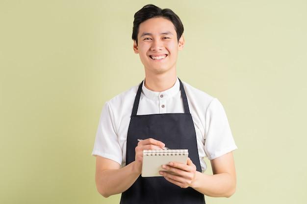 아시아 서비스 직원이 고객의 요청을 기록하고 있습니다.