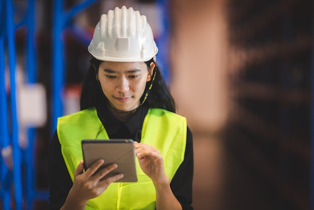 Менеджер азиатского склада, проектирующий, проверяет запасы и упаковку магазина на грузовом промышленном заводе.