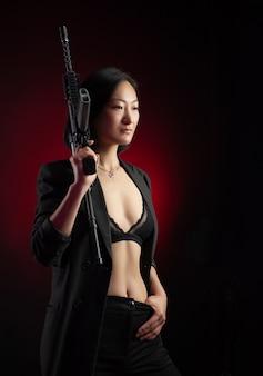 그녀의 손에 자동 소총이 있는 재킷을 입은 아시아 여성 마피아 전투기