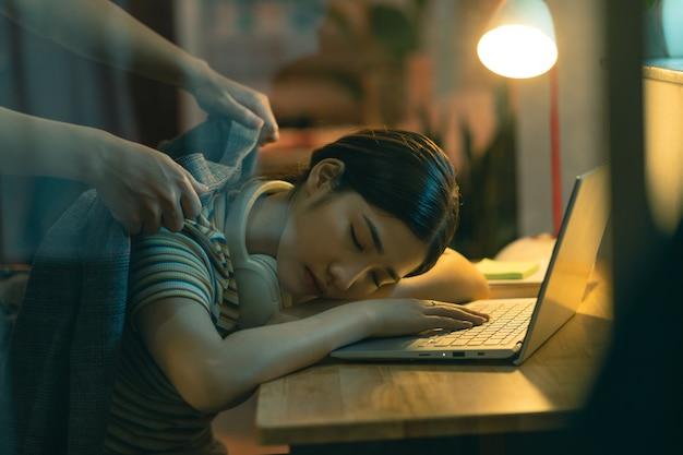 アジアの女性は夜働いている間に眠りに落ちています、夫は眠っている妻を覆っています