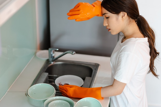 아시아 여성이 피곤한 기분으로 설거지를 하고 있다